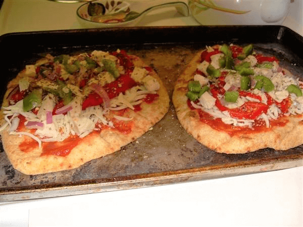 naan whole-grain flatbread, pizza sauce, Veggie Shreds mozzarella cheese, red bell peppers, yellow bell peppers, orange bell peppers, green bell peppers, sweet onions, Vidalia onions, mushrooms, turkey pepperoni